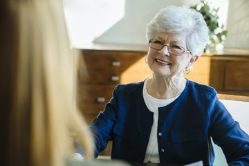 Smiling senior woman discussing with financial advisor in office