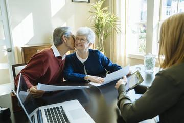 Senior man kissing senior woman while sitting in financial advisor's office