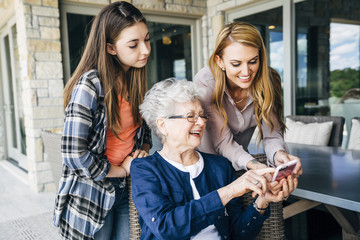 Mid adult woman using smart phone with mother and daughter on porch