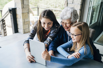 High angle view of granddaughters using tablet computer with grandmother on porch