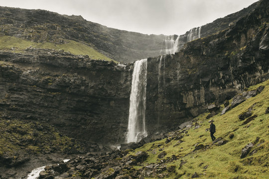 Hiker standing on mountain against waterfall