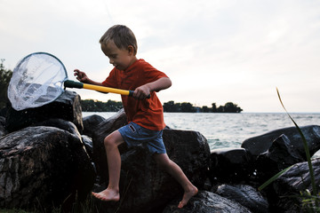 Playful boy running on rocks while holding butterfly fishing net against sea and clear sky