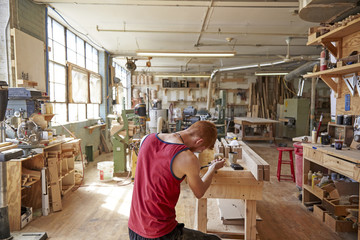 Rear view of carpenter working in workshop