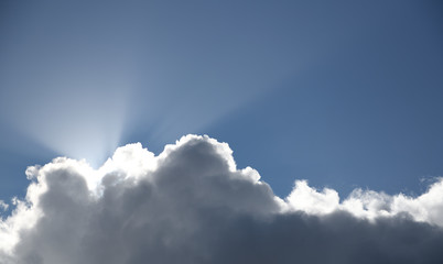 Aluminium Prints Heaven sun rays shining from behind a thick cloud on clear blue sky
