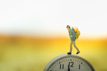 Travel and time concept. Traveler miniature people figure walking on watch.