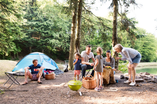Beautiful family camping in forest, eating together.