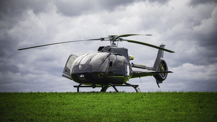 Foto op Canvas Helicopter Black helicopter standing on the green grass