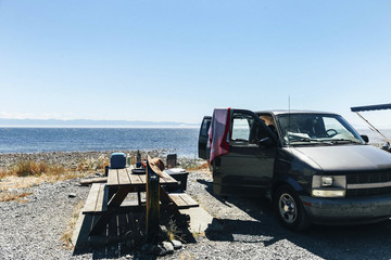 Picnic table and open car at shore against sea and clear sky during sunny day