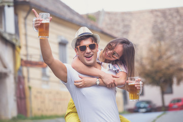 Young happy couple with beer on the street