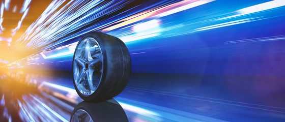 Reifen auf Alufelge fährt schnell durch eine Stadt bei Nacht