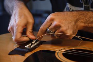 liutaio applica le corde ad una chitarra classica