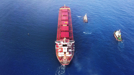 Large bulk carrier ship pulled by tugboats in open water