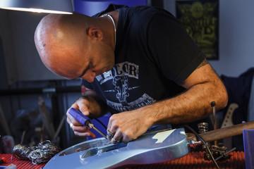 maestro liutaio salda componenti elettronici di una chitarra