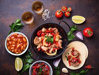 Concept of Mexican food.  Salsa, tortilla, beans, fajitas and te