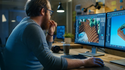 Creative Male Game Developer Works with Graphics for the New Level Design, He Sits at His Wooden Table Working on Two Display Personal Computer. Other People Work in This Creative Studio.