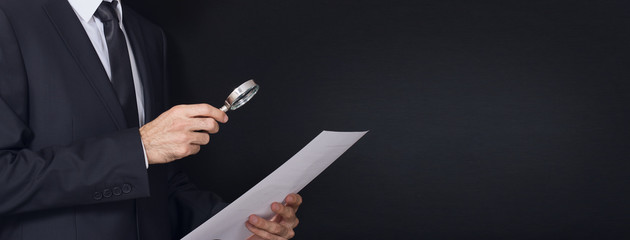suit man examines document with magnifying glass