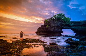Photography take photo of Tanah Lot Temple on sea at sunset in Bali Island, Indonesia.