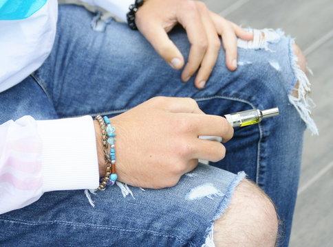 jeune homme et cigarette électronique,détail