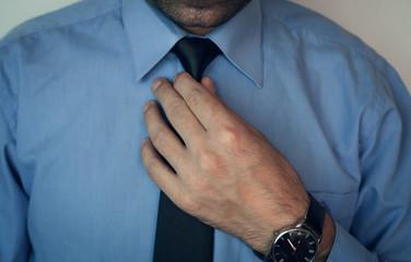 Business Man fixing his tie.