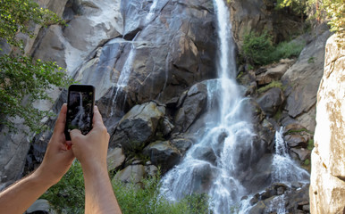 Man is holding a smart phone and taking pictures of a waterfall. Hiking man use smart phone making photo of mountain landscape with a waterfall.