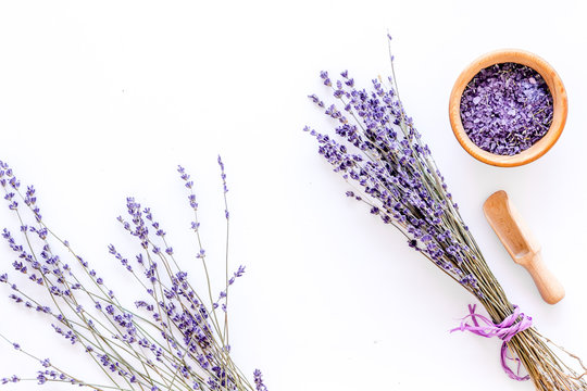 home spa with lavender herbs cosmetic salt for bath on white desk background top view mock-up