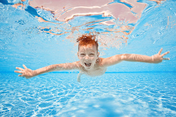 Happy young boy swim and dive underwater, kid breast stroke with fun in pool. Active healthy lifestyle, water sport activity and lessons with parents on summer family vacation with child