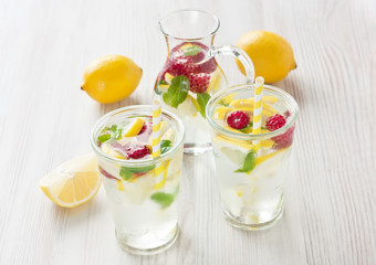 Fresh lemon and raspberry water drink / Fresh lemon and raspberry cold water drink lemonade with mint in two glass