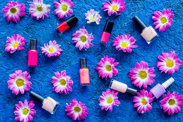 Preparing for manicure. Nail polishes on blue background with flowerrs top view