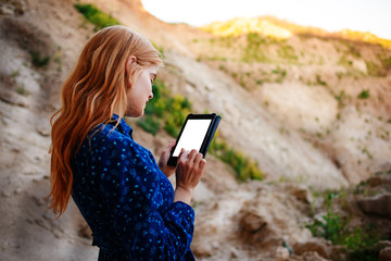 Woman looking at the screen of a tablet on the background of a sand quarry