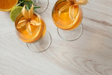 Refreshing cold orange cocktails decorated with physalis, lime and rosemary top view
