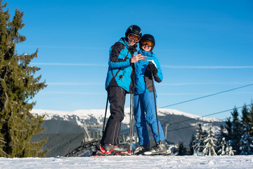 Couple skiers standing on mountain top together at a winter resort with ski lift and blue sky in background. Dressed at blue warm clothing, helmets and goggles. Man holding telephone. Sunny winter day