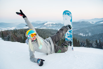 Shot of a happy young woman snowboarder lying on the snow having fun outdoors resting in the mountains after riding happiness recreation winter sports concept