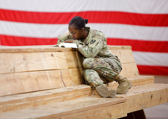Specialist Spencer reads her bible while waiting for her unit from the 602nd Area Medical Support Company to depart for St. Thomas in the U.S. Virgin Islands, at Fort Bragg