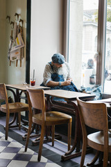 Cool Elderly Man With Long Grey Hipster Beard Sewing in Bright Restaurant