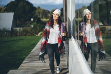 Woman walking with yoga mat