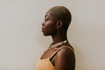 Side profile portrait of a beautiful black woman with a shaved head.