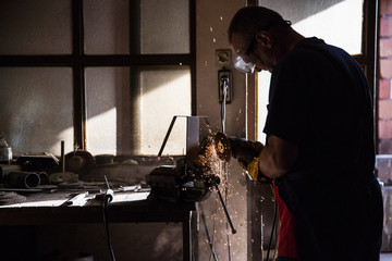 A man in a workshop using an industrial metal grinder to grind down stainless steel