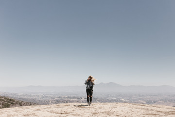blonde fashionable woman in the desert mountains