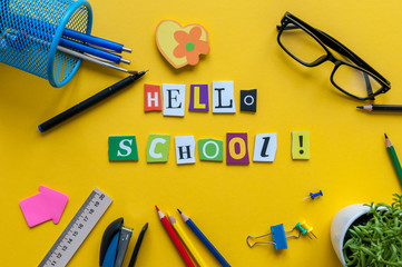 Hello School. Items for the school on a yellow table. Pupil outfit. Back to school concept