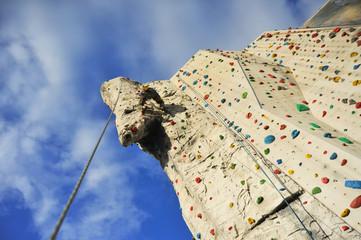 Kletterer in der vertikalen Außenkletterwand einer Kletterhalle bei der Überwindung eines Überhangs