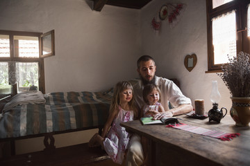 Father reading a book to his little daughters at home
