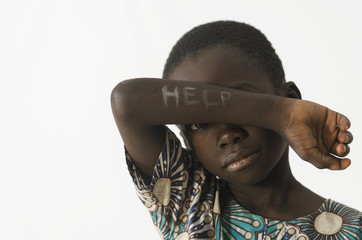 Littel African boy asks for help by covering his face with his arm, isolated on white