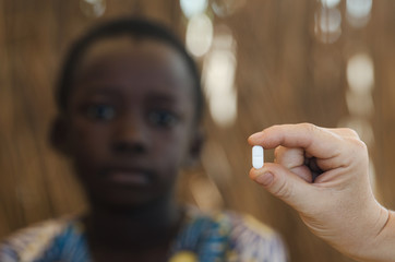 Young African boy getting a medicine pill by a white doctor