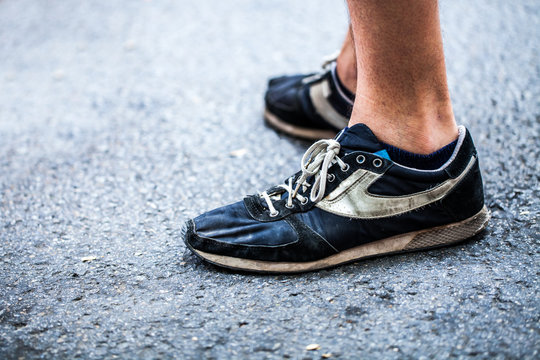 Man close up view of shoes in wet asphalt