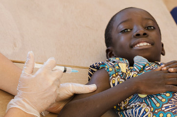 Black boy smiles ready to get his first needle injection from a European volunteer