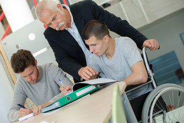 student in wheelchair working in assitance class