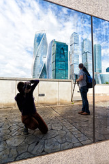 Moscow, Russia young photographers take pictures of the skyscrapers in the reflection in the window