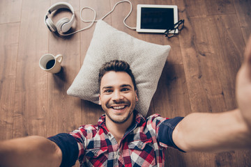 Funky swag selfie! Break, relax, pause, chill serene time after studies. Brunet teen hipster with bristle is taking shot, extremely joyful, wearing checkered shirt, resting on the floor at home