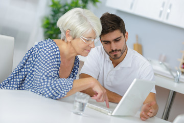 young man helping elderly woman surfing on the web