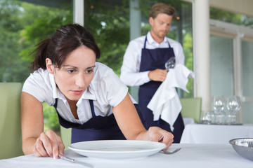 waitress setting the table in a restaurant
